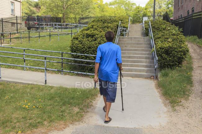 Hombre con lesión cerebral traumática caminando por su vecindario - foto de stock