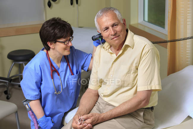 Nurse with Cerebral Palsy checking the ears of a patient in a clinic — Stock Photo