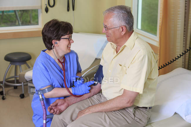 Nurse with Cerebral Palsy taking a patient's blood pressure in a clinic — Stock Photo