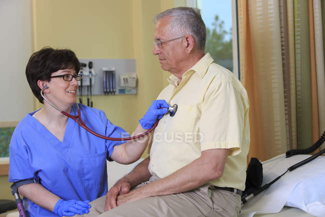 Nurse with Cerebral Palsy checking a patient's heart in a clinic — Stock Photo