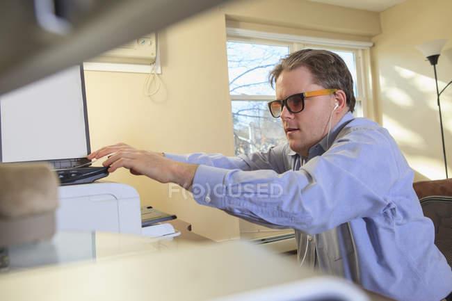 Hombre con ceguera congénita escaneando papeleo en su computadora - foto de stock