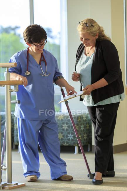 Infirmière avec paralysie cérébrale vérifiant avec administration les dossiers d'un patient dans une clinique — Photo de stock