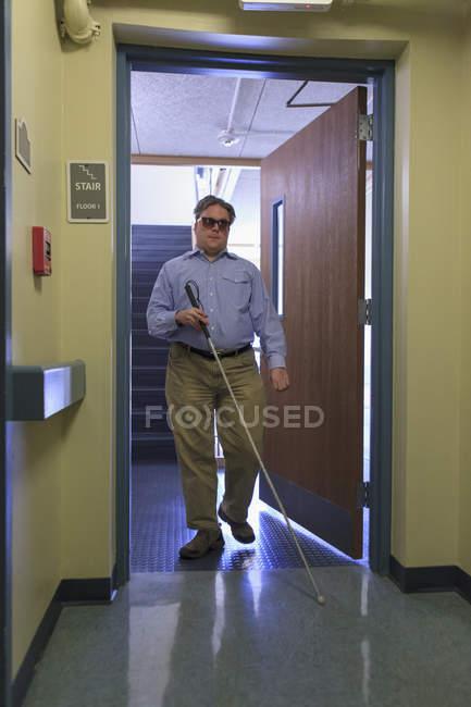 Человек с врожденной слепотой, используя трость, чтобы пройти через дверной проем — стоковое фото