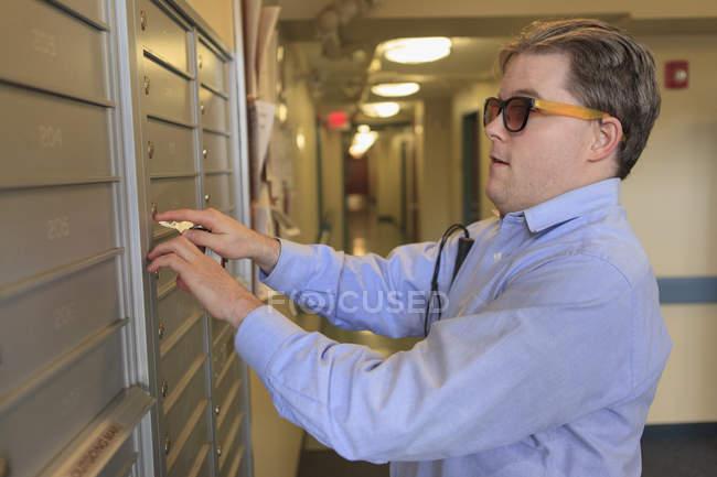 Мужчина с врожденной слепотой вскрыл почтовый ящик в своем многоквартирном доме — стоковое фото