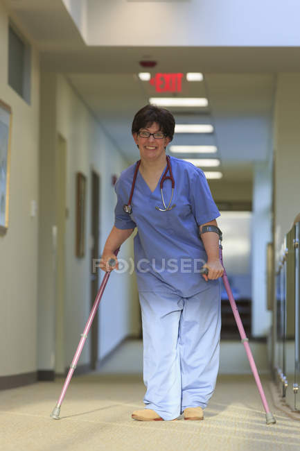 Nurse with Cerebral Palsy walking down the hallway of a clinic with her canes. - foto de stock