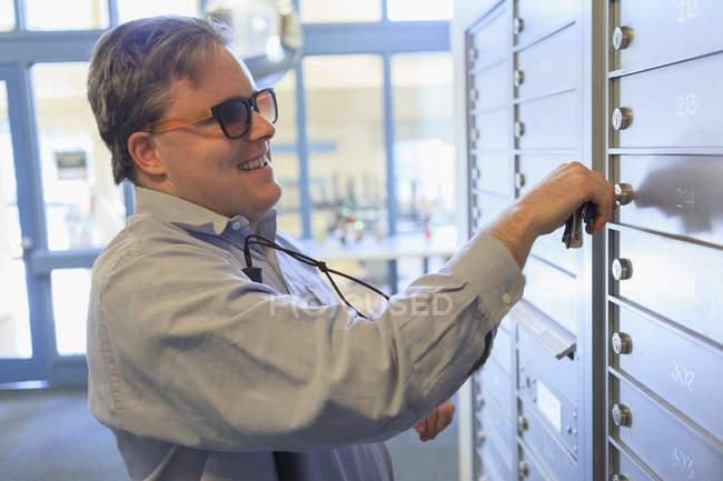 Hombre con ceguera congénita abriendo su buzón en su edificio de apartamentos - foto de stock