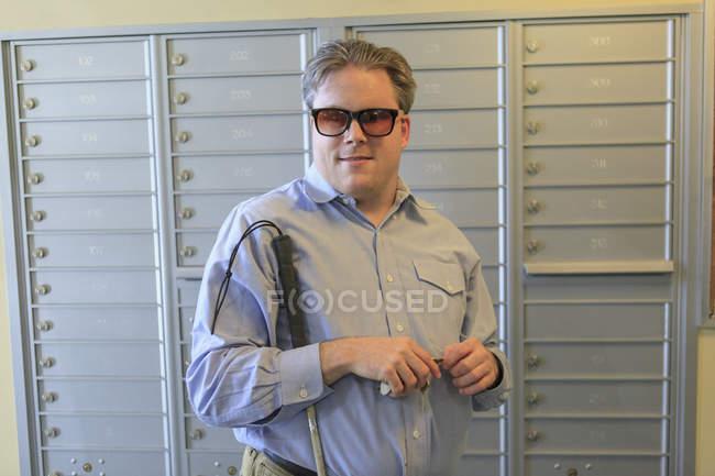 Мужчина с врожденной слепотой у почтового ящика в своем многоквартирном доме — стоковое фото