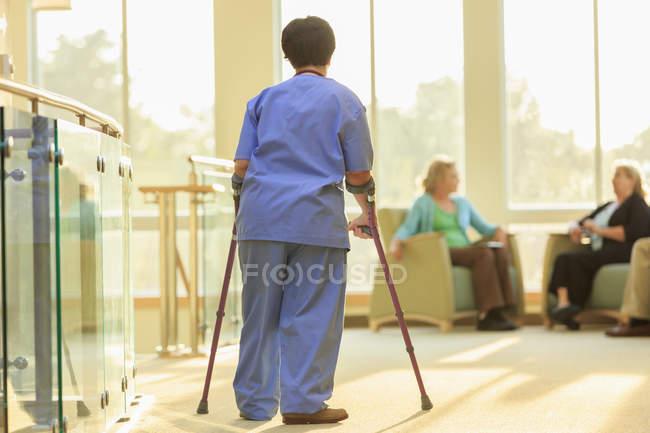 Infirmière avec paralysie cérébrale marchant dans le couloir d'une clinique avec ses cannes — Photo de stock