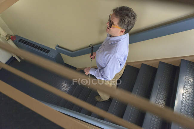 Человек с врожденной слепотой с помощью трости спускается по лестнице — стоковое фото