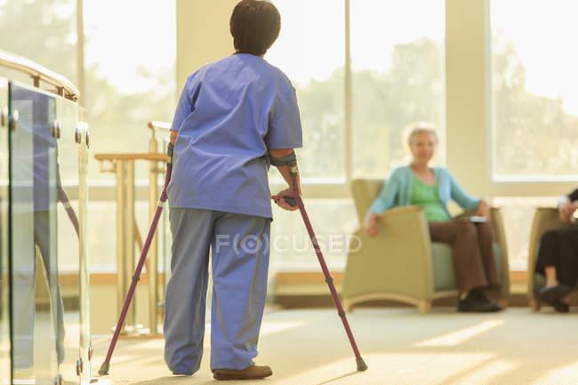 Медсестра з Церебралем Пальсі йде по коридору з тростинами в клініці. — стокове фото