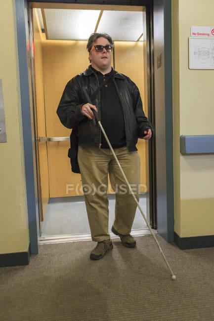 Человек с врожденной слепотой выходит из лифта — стоковое фото