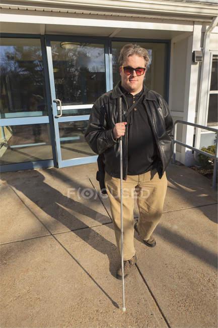 Hombre con ceguera congénita saliendo de su edificio de apartamentos - foto de stock