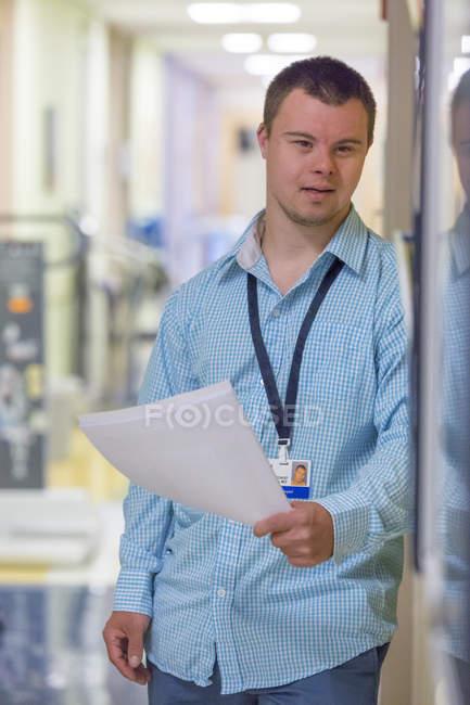 Homem com síndrome de Down que trabalha na área do hospital — Fotografia de Stock