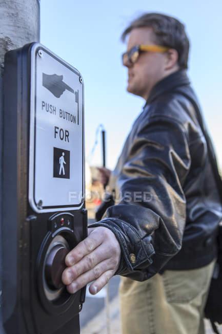 Hombre con ceguera congénita presionando el botón de la luz de la calle para detener los coches para que pueda cruzar - foto de stock