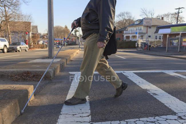 Мужчина с врожденной слепотой переходил улицу с тростью — стоковое фото