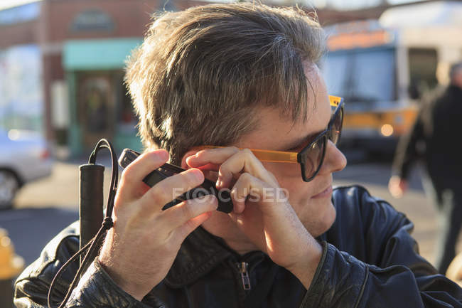 Man with congenital blindness using  assistive technology to listen on the street — Stockfoto