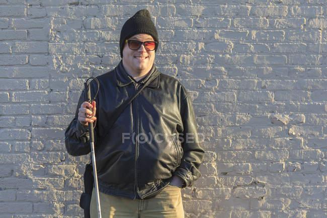 Человек с врожденной слепотой стоит перед стеной с тростью — стоковое фото