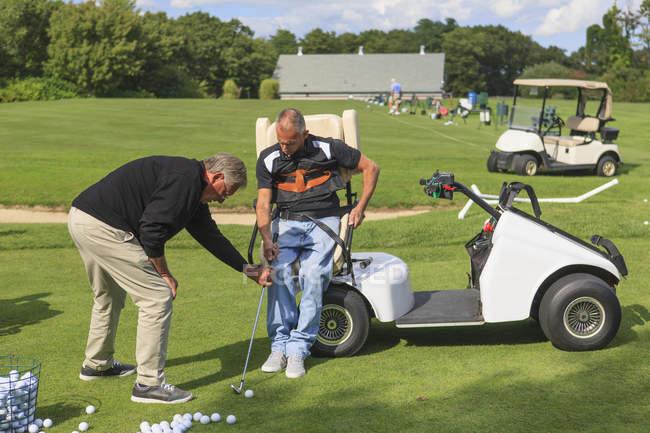 Mann mit Querschnittslähmung in einem adaptiven Cart auf dem Golf Putting Green mit einem Trainer — Stockfoto