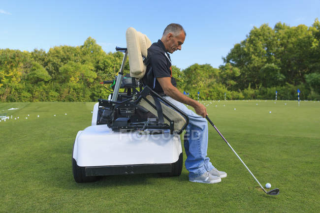 Man with spinal cord injury in an adaptive cart at golf putting green — Stock Photo