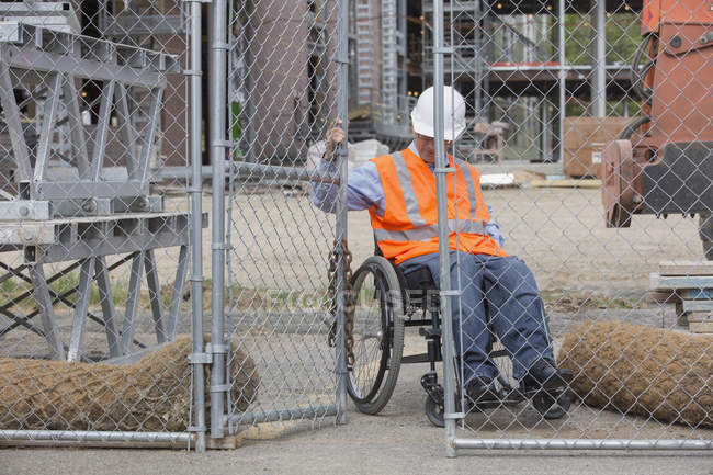 Project engineer with a Spinal Cord Injury in a wheelchair closing fence to job site — Fotografia de Stock
