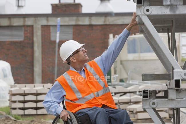 Project engineer with a Spinal Cord Injury in a wheelchair at job site - foto de stock