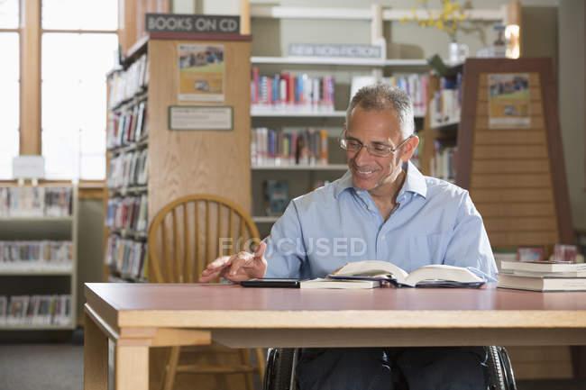Hombre con una lesión en la médula espinal en una biblioteca leyendo una tableta - foto de stock
