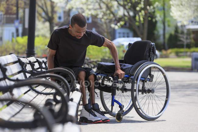 Homme qui avait une méningite rachidienne sortant d'un banc du parc et se rendant dans son fauteuil roulant — Photo de stock