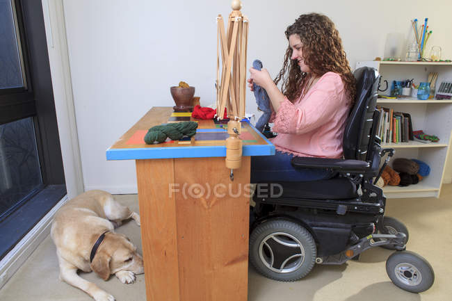 Woman with Muscular Dystrophy working with her yarn for her knitting business - foto de stock