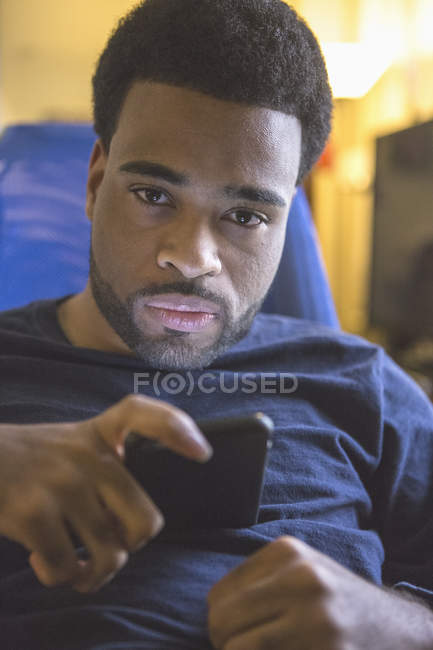 African American man with Cerebral Palsy using his cell phone at home — Stock Photo