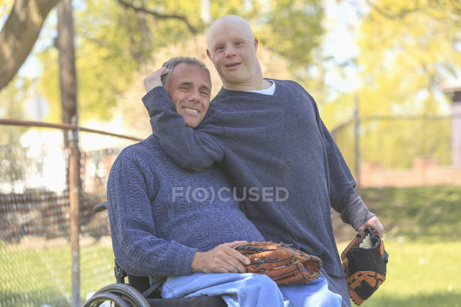 Father with Spinal Cord Injury and son with Down Syndrome about to play baseball in park — Stock Photo
