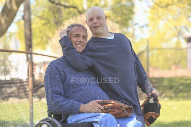 Padre con lesione al midollo spinale e figlio con sindrome di Down che sta per giocare a baseball nel parco — Foto stock