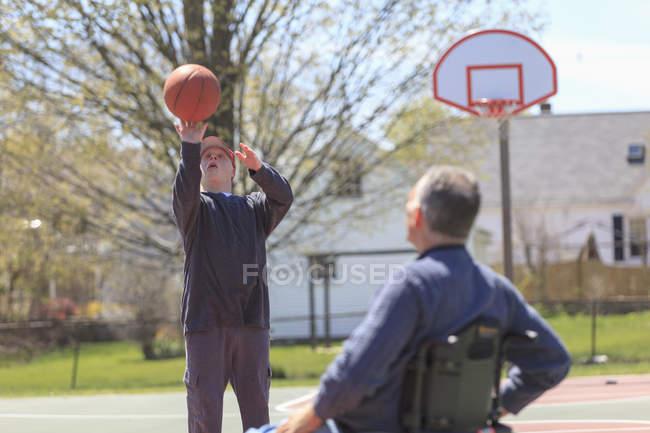 Отец и сын с синдромом Дауна играют в баскетбол — стоковое фото