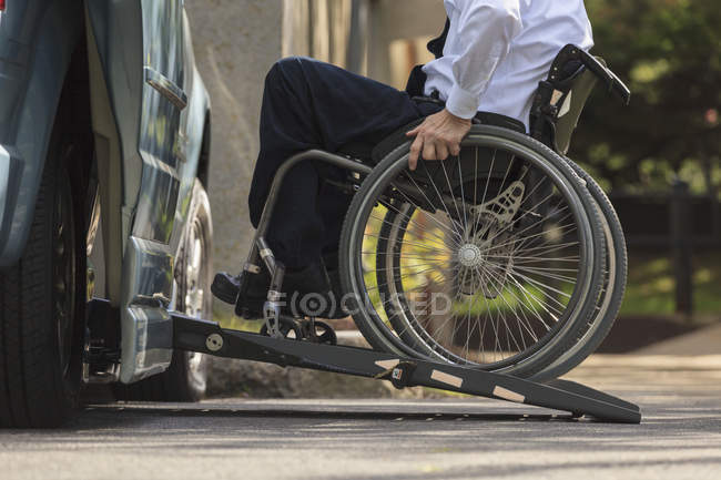 Businessman with Muscular Dystrophy in a wheelchair entering his accessible van in the parking lot — Stock Photo