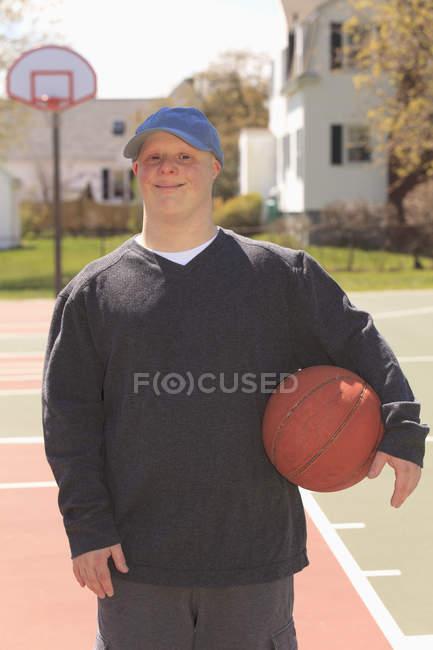 Ritratto di un giovane con sindrome di Down che tiene il basket in par — Foto stock