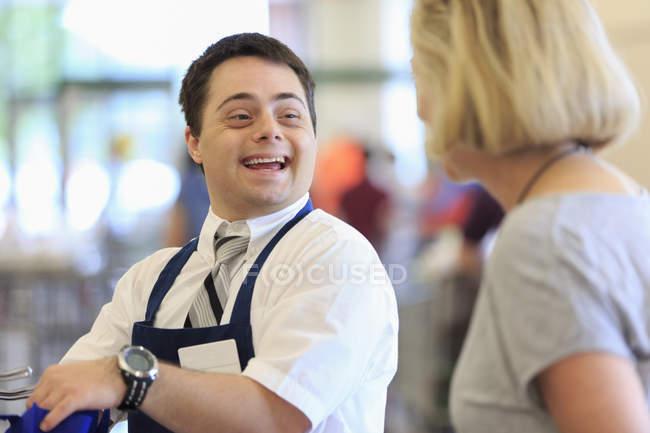 Людина з синдромом Дауна працює в продуктовому магазині — стокове фото