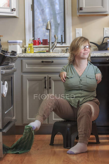 Woman with TAR Syndrome picking up a kitchen towel with her feet — Stock Photo