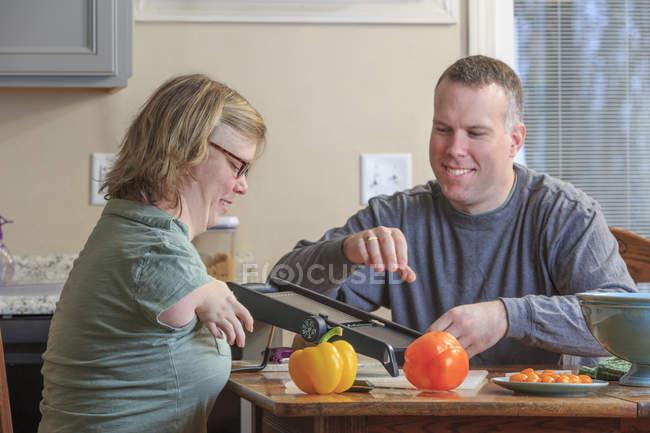 Mujer con Síndrome de TAR y su marido rallando verduras en la cocina - foto de stock