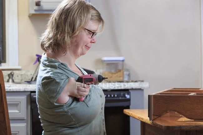 Mujer con Síndrome de TAR usando una sierra eléctrica en casa - foto de stock
