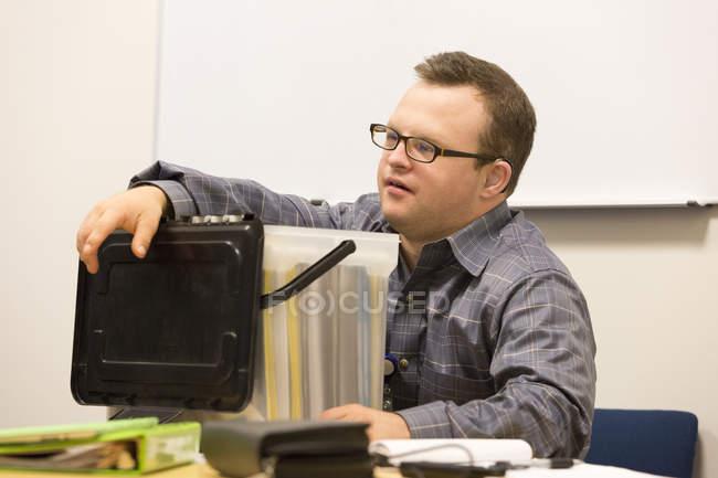 Portrait d'un travailleur humanitaire hospitalisé atteint de trisomie 21 travaillant au bureau — Photo de stock