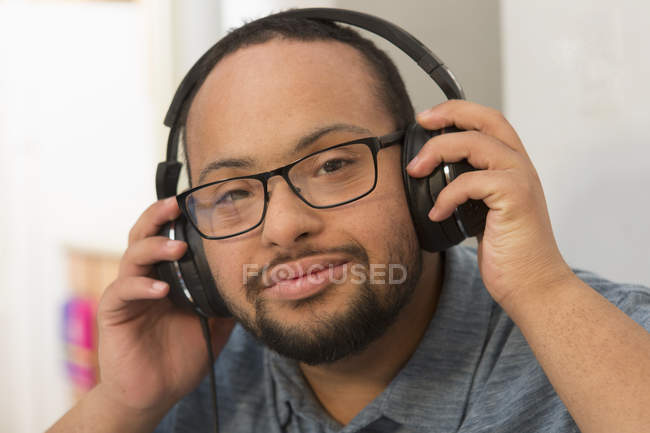 Happy African American man with Down Syndrome listening to music with headphones at home — Stock Photo