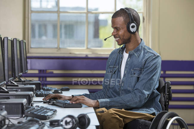 Man who had Spinal Meningitis in a wheelchair working in a call center — Stock Photo