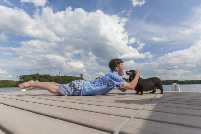 Young man with Down Syndrome playing with a dog on a dock — Stock Photo