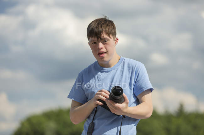 Young man with Down Syndrome holding a camera — Stock Photo