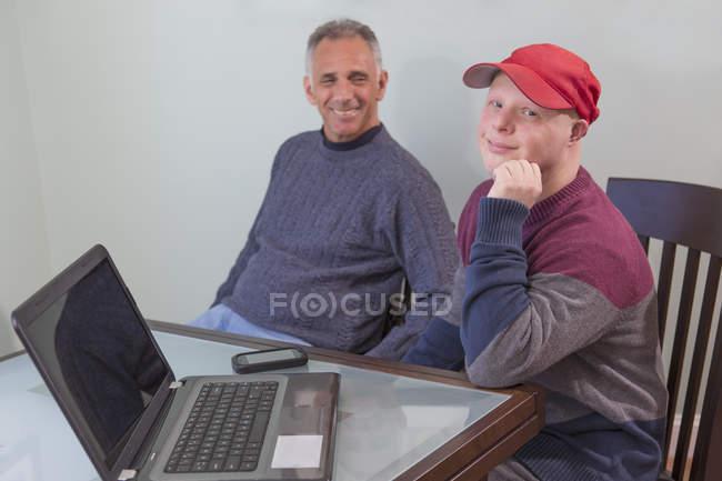 Отец с травмой спинного мозга и сын с синдромом Дауна с ноутбуком дома — стоковое фото