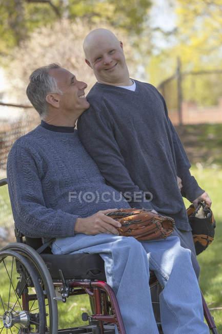 Père avec blessure à la moelle épinière et fils avec trisomie 21 sur le point de jouer au baseball dans le parc — Photo de stock
