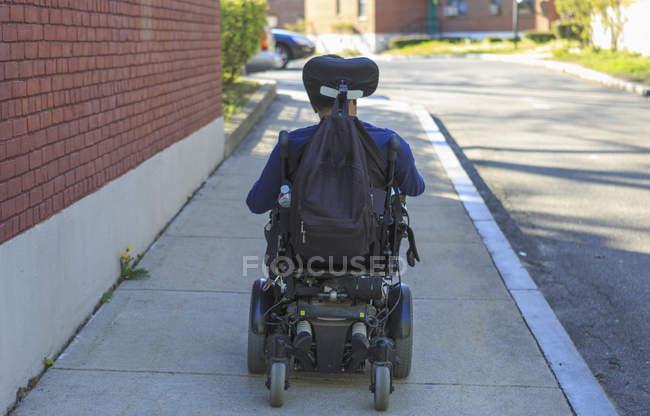 Uomo afroamericano con paralisi cerebrale utilizzando la sua sedia a rotelle potere al di fuori — Foto stock