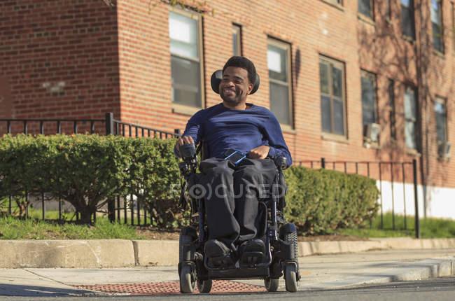 Heureux homme afro-américain atteint de paralysie cérébrale en utilisant son fauteuil roulant électrique à l'extérieur — Photo de stock
