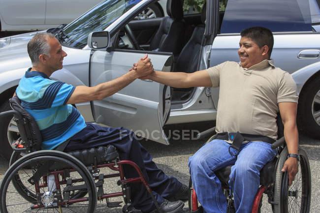 Друзі з травмами спинного мозку у інвалідних візках вітаються. — стокове фото