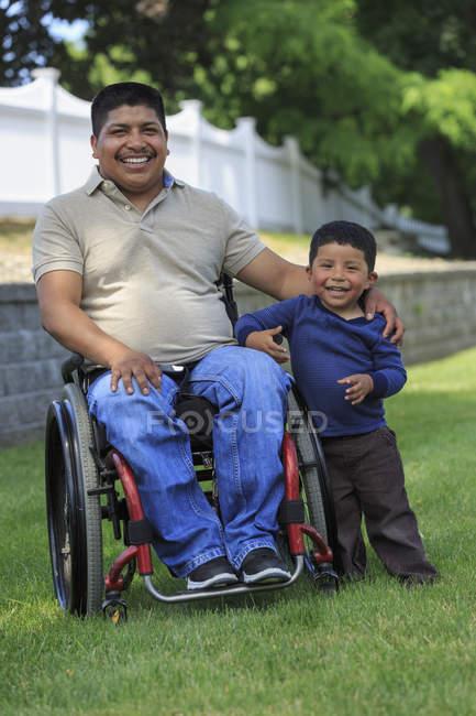 Портрет латиноамериканца с травмой спинного мозга в инвалидном кресле с сыном на газоне — стоковое фото
