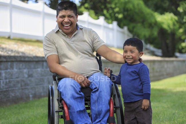 Латиноамериканец с травмой спинного мозга в инвалидном кресле со смехом сына на газоне — стоковое фото